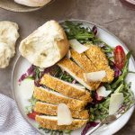Baked parmesan chicken is an easy meal idea! These cutlets are pounded thin, then breaded in browned bread crumbs to make a crispy, oven baked meal perfect over a salad for a light dinner.   justalittlebitofbacon.com #chickenrecipes #dinnerrecipes #chicken #chickenbreast