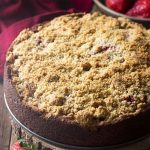 Enjoy a slice of moist and delicious banana strawberry cake! This crumb topped coffee cake with fruit filling is perfect for breakfast, snacks, or dessert. | justalittlebitofbacon.com #cakerecipes #dessertrecipes #coffeecake #bananacake #strawberries #bananas