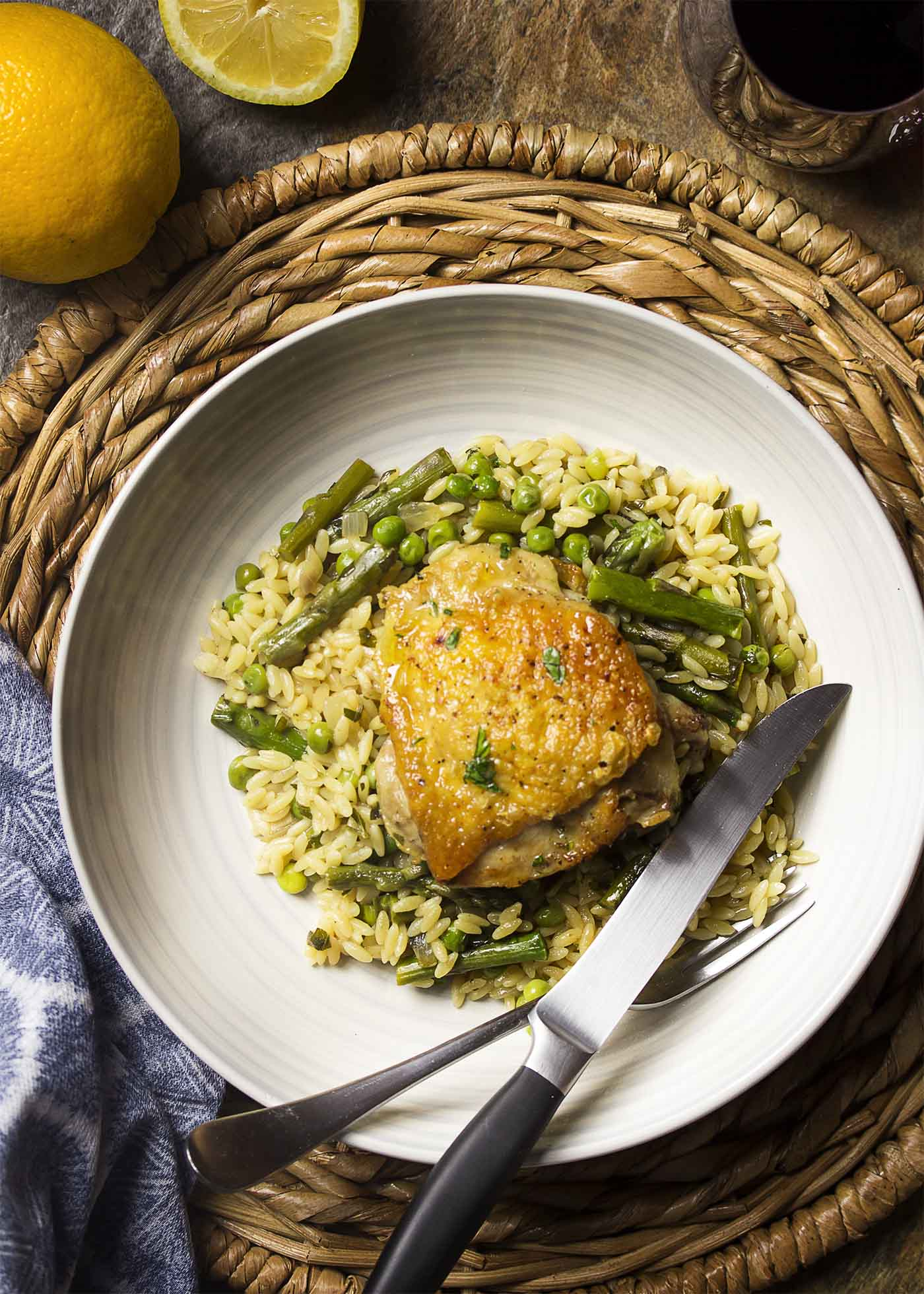 Top view of a bowl filled with orzo and vegetables topped with a golden brown chicken thigh.