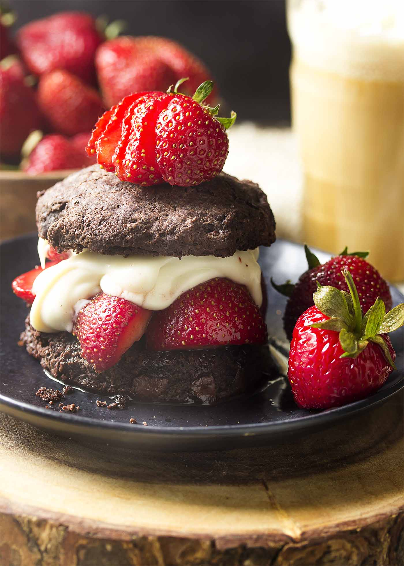 Sliced strawberries and bourbon cream sauce sandwiched between two chocolate biscuits on a plate.