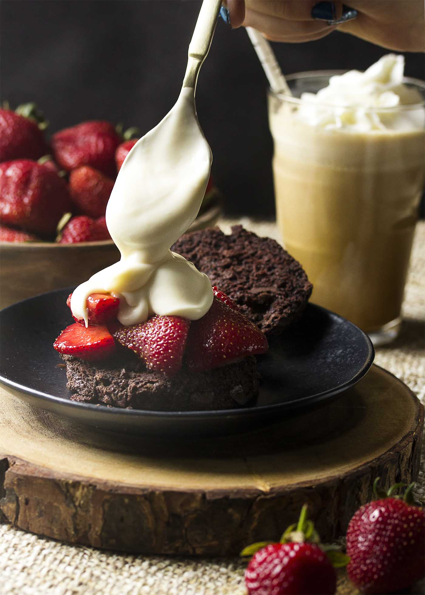 Chocolate biscuit cut open, topped by strawberries. A spoon pouring thick cream sauce over the top.