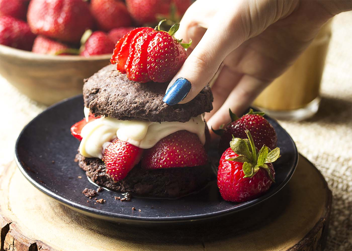 A hand picking up a strawberry shortcake off a black plate.