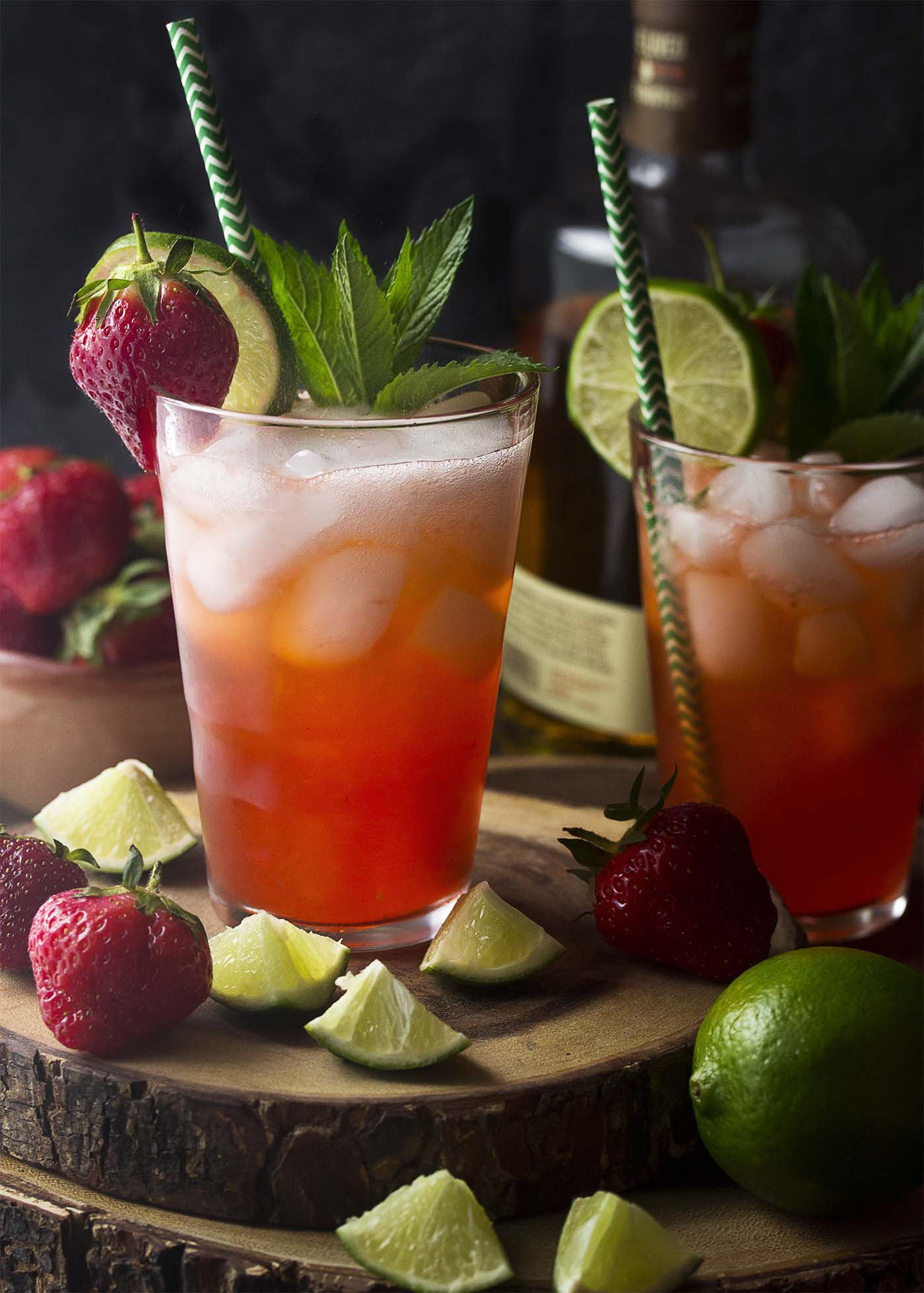 Two fizzy pink mojitos in tall glasses with ice and straws garnished by fruit and mint.