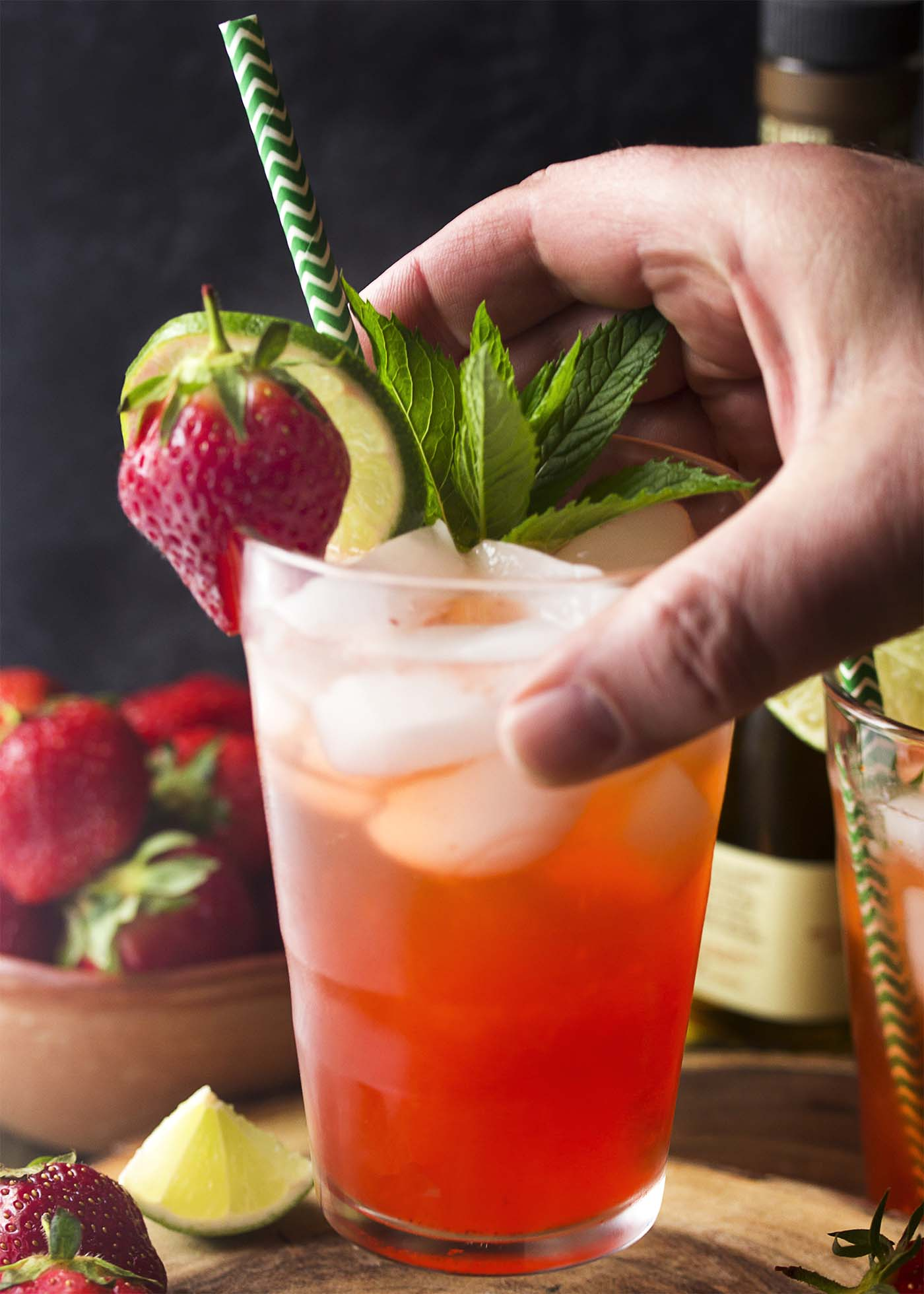 A hand lifting up a pink drink in a tall glass garnished by strawberry, lime, and mint.