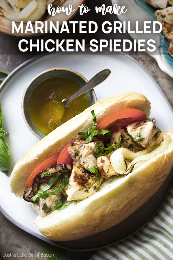 Close up of grilled chicken on a bun with text overlay - Marinated Grilled Chicken Spiedies.