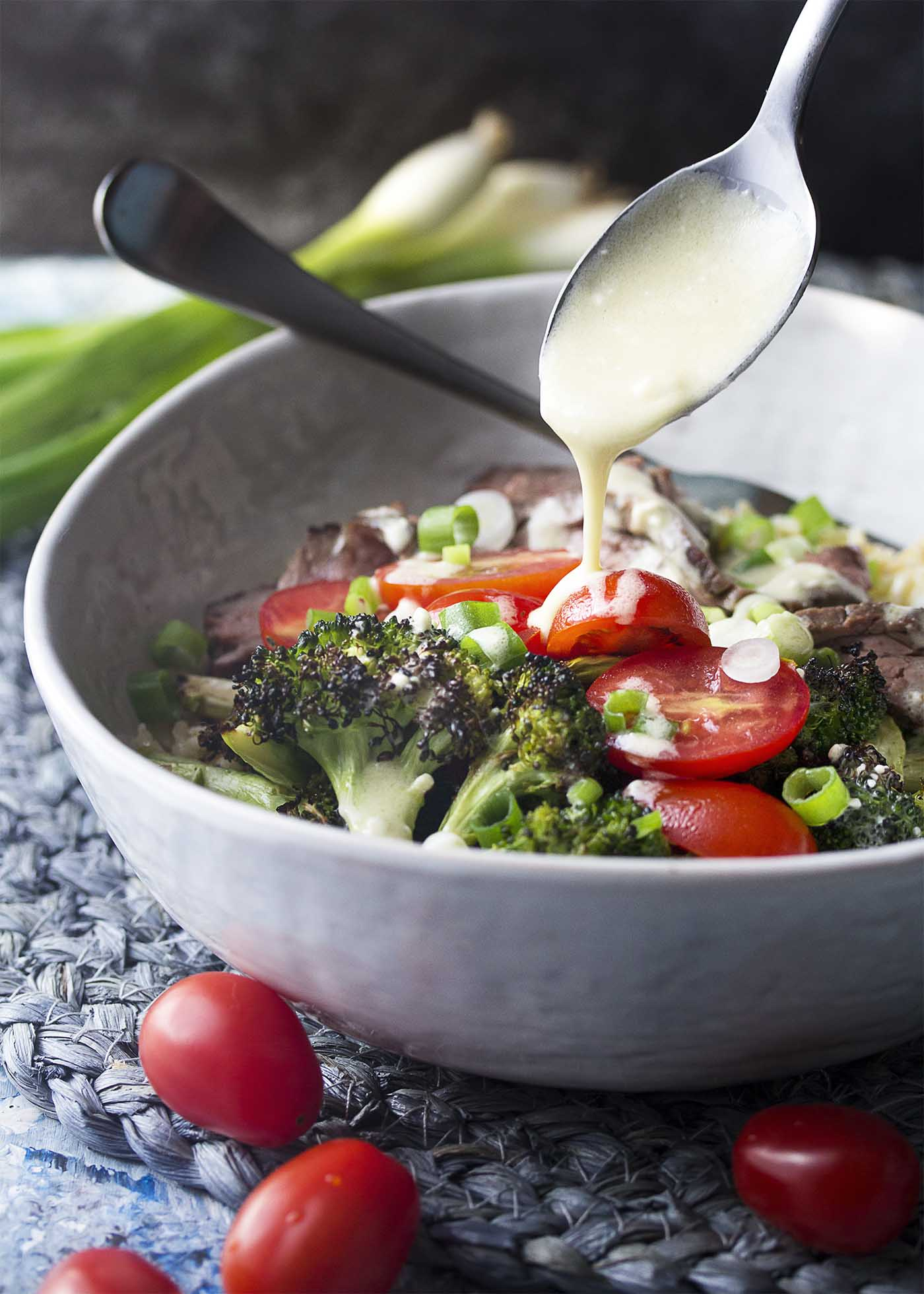A spoon drizzling blue cheese dressing over a bowl filled with grilled steak and broccoli salad.