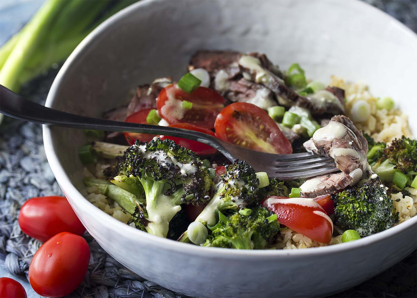 A fork picking up a slice of steak from a bowl of salad all topped by blue cheese dressing.