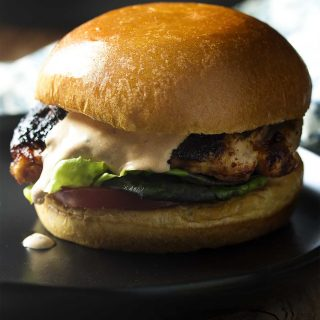 For a quick summer dinner coat chicken thighs with a spicy rub then layer them on brioche buns with chipotle mayo for grilled chicken sandwiches. | justalittlebitofbacon.com