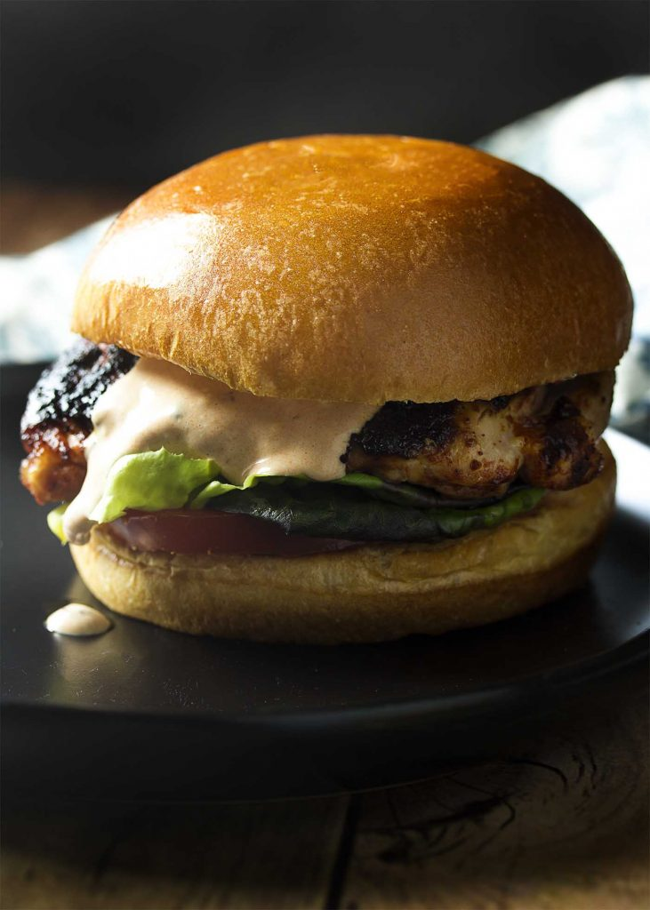 Close up of a spicy grilled chicken sandwich on a brioche bun layered with vegetables and sauce dripping down.