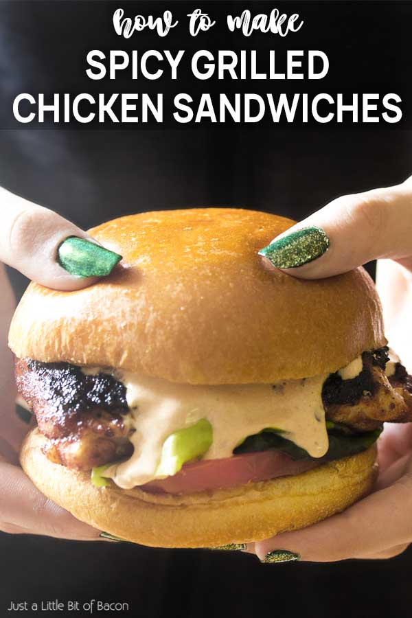 Hands holding grilled chicken on a bun with text overlay - Spicy Grilled Chicken Sandwiches.